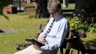 Stock Video Footage of Man with tablet conputer in park