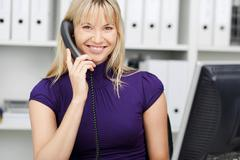 businesswoman conversing on landline phone - stock photo