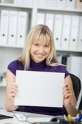 happy businesswoman blank paper at desk - stock photo