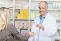 Pharmacist giving medicine bag to customer Stock Photos
