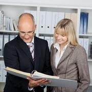 two colleagues reading in binder - stock photo