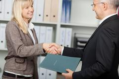Businessman shaking hands with female candidate Stock Photos
