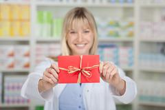 female pharmacist holding wrapped gift in pharmacy - stock photo