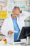 Stock Photo of pharmacist holding prescription paper at counter