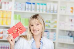 Female pharmacist showing coupon Stock Photos