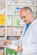Pharmacist holding package and prescription Stock Photos