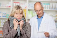 Woman shivering with male pharmacists reading prescription Stock Photos