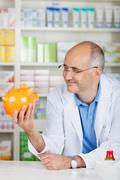 Pharmacist holding piggybank while leaning on counter Stock Photos