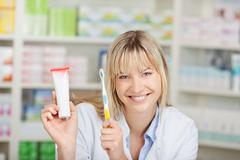 pharmacist holding toothpaste and toothbrush in pharmacy - stock photo