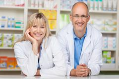 pharmacists leaning on pharmacy counter - stock photo