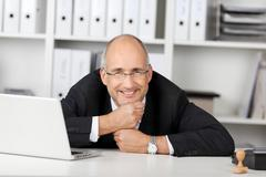 Businessman resting his chin on fists at office desk Stock Photos