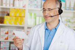 cheerful pharmacist using headset - stock photo