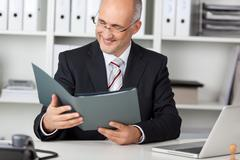 smiling businessmann looking at cv - stock photo