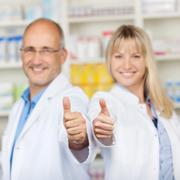 Pharmacists showing thumbs up in pharmacy Stock Photos