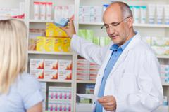 Pharmacist taking out prescribed medicine for customer Stock Photos