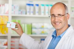 Pharmacist taking medicine from shelf Stock Photos