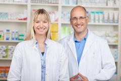 confident male and female pharmacists standing in pharmacy - stock photo