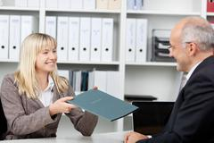 candidate giving application file to businessman - stock photo