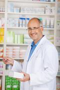 Pharmacist holding medicine and prescription paper in pharmacy Stock Photos