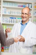 customer's hand paying money to male pharmacist for medicine - stock photo