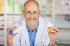 male pharmacist holding toothbrush and toothpaste in pharmacy - stock photo
