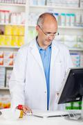 pharmacist looking at computer - stock photo