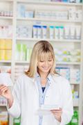 smiling female pharmacist reading leaflet - stock photo