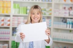 female pharmacist showing white paper - stock photo