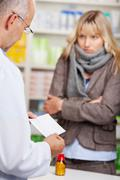 woman with a cold in pharmacy - stock photo
