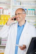 Cheerful mature pharmacist on the phone Stock Photos