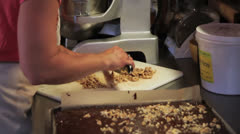 A woman chops fresh walnuts for brownies Stock Footage