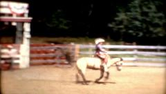 1960s frontier town rodeo cowboy riding a bucking horse vintage Stock Footage