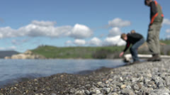 Kids collecting rocks to skip on lake shore - stock footage