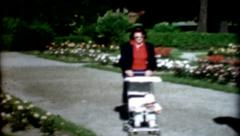 1960s female pushing baby stroller checks on baby vintage fashion Stock Footage