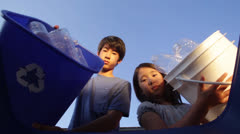 Asian Children Recycle Plastic Bottles by Throwing into a Bin - Slow Motion - stock footage