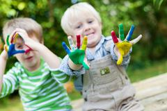 happy children playing with finger paint - stock photo