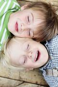 smiling little brothers lying close together - stock photo