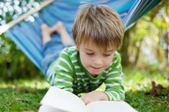 Cheerful little boy reading book in the hammock Stock Photos