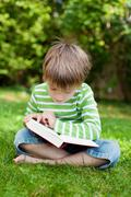 cute young boy sitting on grass and reading - stock photo