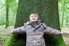 Little boy leaning on big tree Stock Photos