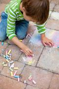 Boy playing with chalk on pavement Stock Photos