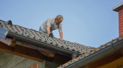 Man Adding New Top Roof Tile Stock Footage