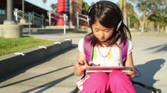 Asian Child Girl Uses Tablet Computer on School Campus - Handheld Shot Stock Footage