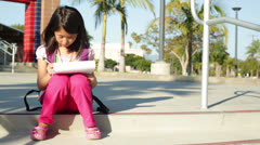 Asian Girl Child Does Homework on School Campus - Handheld Shot Stock Footage
