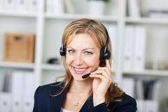 Female customer service operator using headset in office Stock Photos