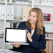 businesswoman displaying laptop with blank screen - stock photo