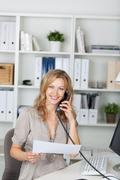 Stock Photo of businesswoman holding paper while communicating on landline phon