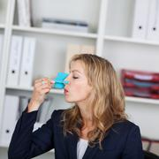 Businesswoman with clip on her nose in office Stock Photos