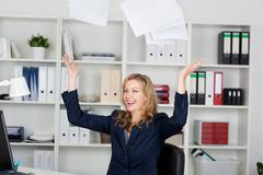 Businesswoman throwing documents in office Stock Photos