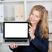 businesswoman displaying laptop with blank screen in office - stock photo